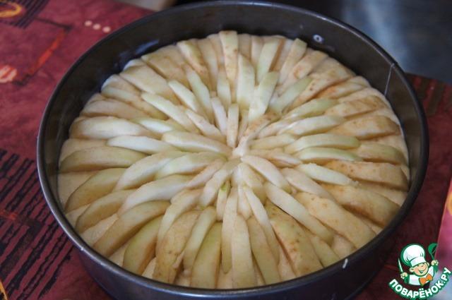 Яблоки очистить, освободить от семян и кожицы, нарезать тонкими дольками. Воткнуть в тесто по кругу выпуклой стороной вверх, плотно друг к другу по всей поверхности пирога (чем больше яблок, тем пирог получится сочнее).
