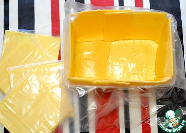 Прямоугольную глубокую форму застелить пищевой плёнкой. Квадратный бутербродный сыр выложить на дно и по бокам формы.