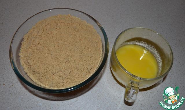 Вливаем растопленное сливочное масло в емкость с печеньем и тщательно перемешиваем ингредиенты.