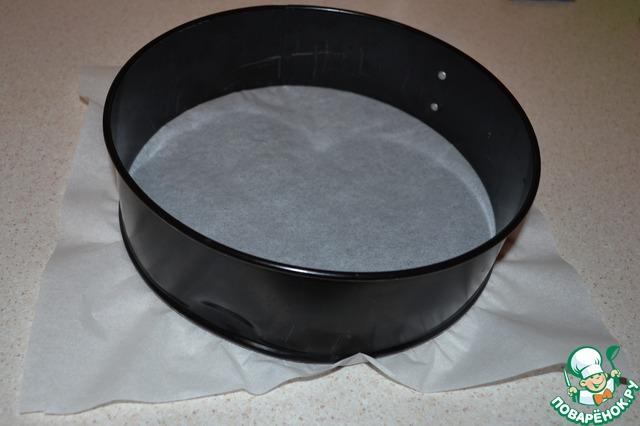 Пока масло остывает, застилаем дно формы пергаментной бумагой. Съемную часть формы я не застилаю пергаментом, бортики никогда не пригорают и не прилипают, я на всякий случай провожу ножом между формой и основой, а потом легко снимаю форму. Советую не обрезать края пергаментой бумаги, тогда будет легче переместить готовый чизкейк на блюдо для подачи.