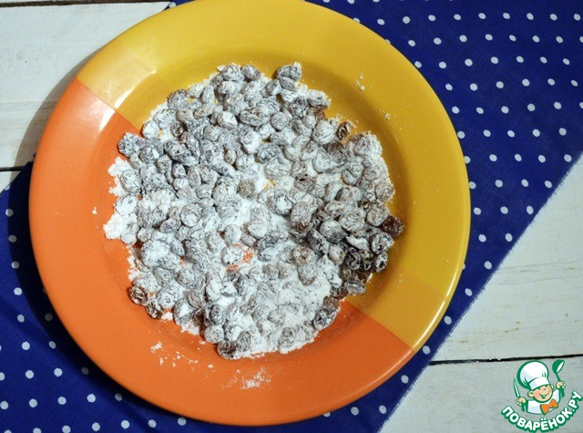 Сухие изюм и вяленую вишню хорошо обваливаем в 1 ст. л. сахарной пудры! Эта процедура нам нужна для того, чтобы они хорошо распределились в тесте, а не сбились в одну кучу.   Выкладываем тесто на слегка припыленную мукой поверхность и аккуратно вмешиваем в него изюм и вишню. Если тесто слишком липнет к рукам, то совсем немного припыляем его мукой.