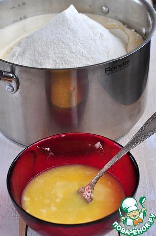 Переложить опару в большую емкость, добавить взбитые яйца, всыпать 2 кг муки, влить теплое масло, добавить растительное масло.