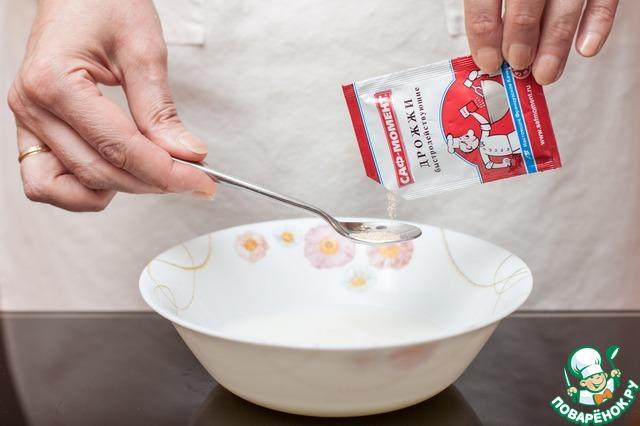 Молоко смешайте с водой, подогрейте жидкость до 38С и всыпьте 2 столовые ложки сахара и сухие дрожжи САФ-Момент. Перемешайте и оставьте на 10 минут до появления пенной шапочки.