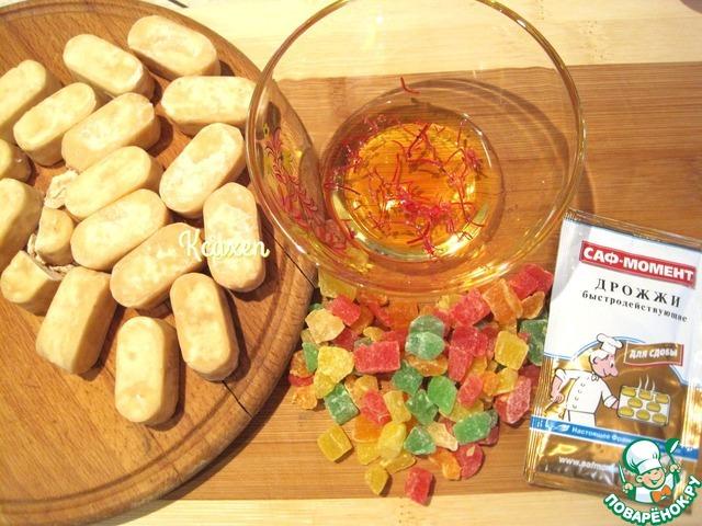 Конфеты и цукаты крупно порубим. Шафран зальём двумя столовыми ложками горячей воды и дадим настояться.