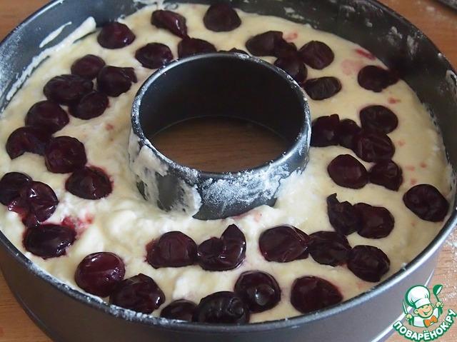 В форму, смазанную маслом и посыпанную мукой, выложить половину теста, сверху выложить вишню.    Если используете мороженую вишню, то ее нужно разморозить.
