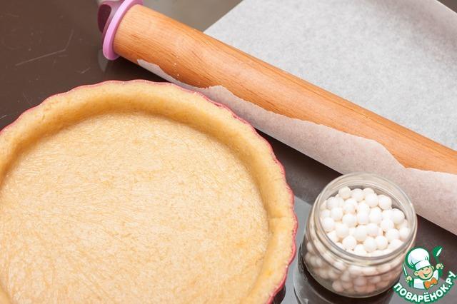 Охлажденное тесто положить между двумя листами пергамента и раскатать в пласт по размеру формы (24-25см). Форму смазать сливочным маслом, выложить в нее тесто, лишнее обрезать скалкой.