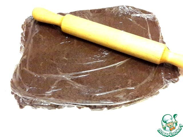 Между двумя кусками пищевой пленки распределите массу равномерно, слегка прокатайте скалкой для получения равномерного пласта