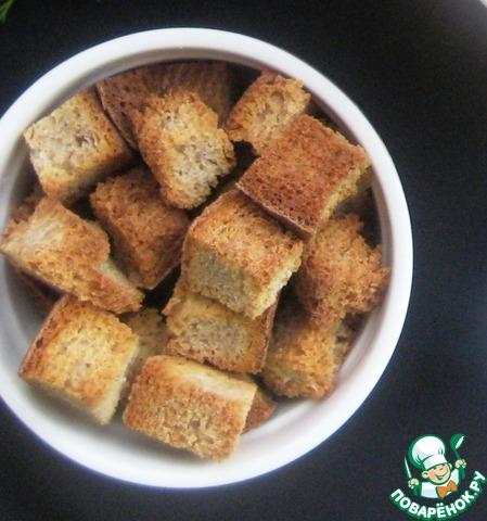 Ломтики хлеба нарезать кубиками и подсушить в разогретой духовке.