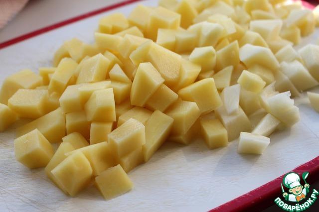 Чечевицу промыть, залить 2 л воды и поставить на огонь. Варить 20 минут после закипания. Пока чечевица готовится, картофель почистить и нарезать достаточно крупными кубиками.