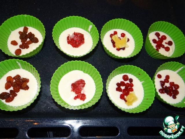 В серединку кладём примерно по 0,5 ст. л замороженных ягод. Я делала с брусникой, вишней без косточки, малиной, с изюмом, и т. д. На фото показаны примеры начинки. Но больше всего мне нравится с черникой! В конце рецепта фото будут именно с ней. Сверху кладём чуть меньше ст. л творожного теста, закрывая ягодки. В итоге формочка будет заполнена где-то на 2/3. Тесто поднимется в процессе приготовления. Убираем формочки в духовку (на протвине или на решетке). Выпекаем до золотистости, примерно 20-25 минут.