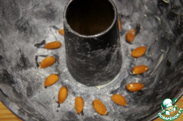 Посыпать пластинками миндаля дно формы или поштучно выложить в выемки ёмкости ядра орехов.