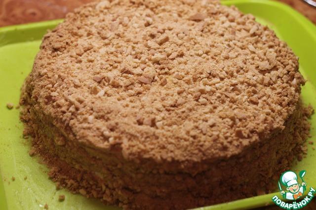 На последний корж и бока торта наносим толстый слой крема, затем посыпаем крошкой. Бока нужно формировать тщательно, чтобы получилось красиво и ровно.