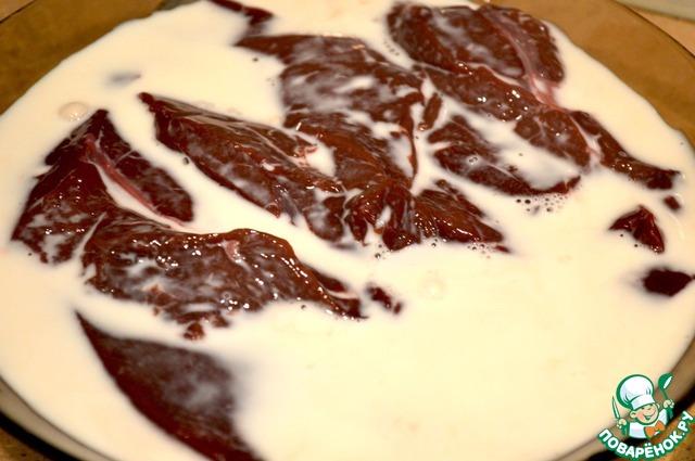 Печенку вымыть, снять пленку и убрать прожилки. Нарезать на порционные кусочки. Залить молоком и убрать в холодильник на 1-2 часа.