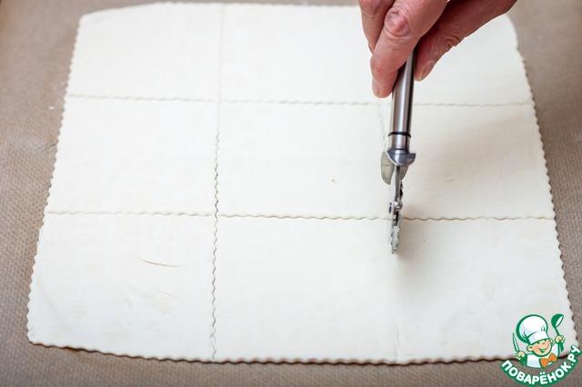 Предварительно размороженное слоеное тесто раскатать в квадрат размером 30х30 см и разрезать на квадраты со стороной 10 см. Также поступить со вторым листом.
