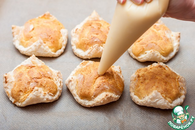 Наполняем корнетик остывшим кремом и заполняем пирожные. Готовые пирожные посыпаем сахарной пудрой.