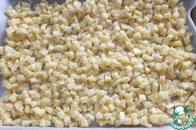 На противень, застеленный пекарской бумагой равномерно в один слой выкладываем картофель.