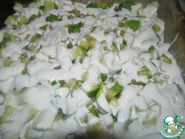 Мелко нарежьте лук, чеснок порубите, без центрального стержня, кабачки нарежьте средним кубиком и обжарьте в масле сначала лук и чеснок до легкого зарумянивания, затем очень недолго кабачки, посолите и тертый мускатный орех по вкусу. Переложите эту очень ароматную смесь в жаропрочную форму.