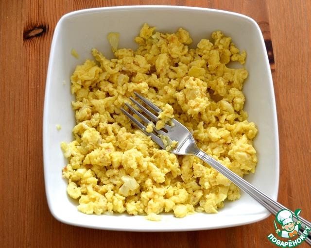 Как только яйца поджарятся (на это уйдет около 1-2 минут), переложить их в тарелку и размять еще вилкой, разбивая на мелкие комочки.