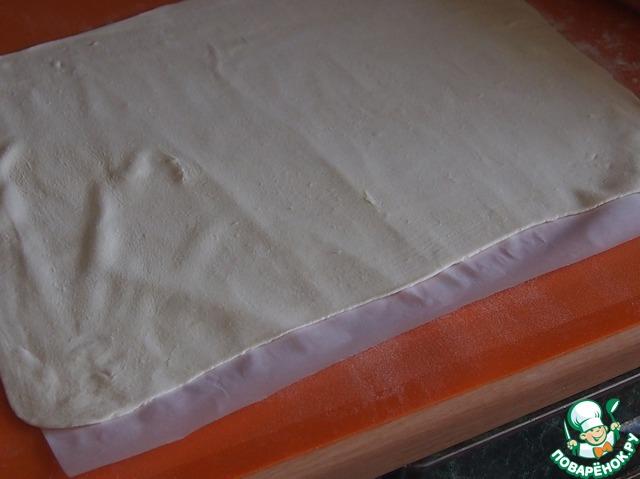 Противень застелить бумагой для выпечки. Слоеное тесто разделить на две части, раскатать в прямоугольник, длинная сторона которого примерно равна длине противня, толщина теста примерно 3 мм. Перенести тесто на отдельный лист бумаги для выпечки. То же самое проделать с другой половиной теста.
