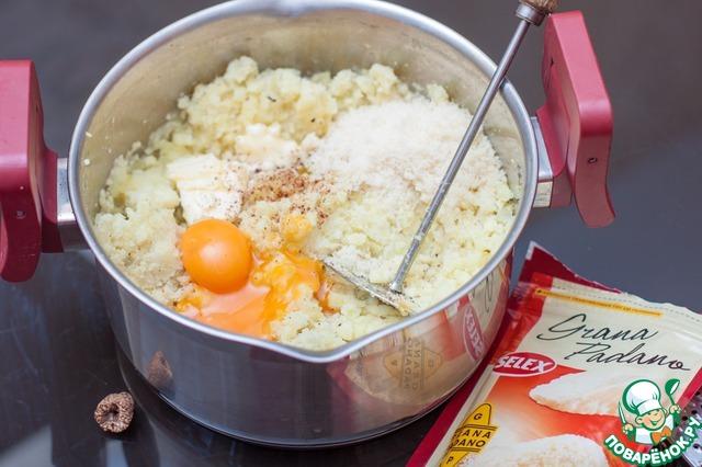 Добавить к картофелю тертый пармезан, желтки, сливочное масло, чесночный порошок и мускатный орех. Тщательно потолочь картофель толкушкой и, при необходимости, протереть через сито. Ни в коем случае не взбивайте пюре блендером - будет резиновое!