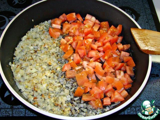 К луку добавить мелко нашинкованные помидоры и измельченный чеснок. Все перемешать и обжарить.
