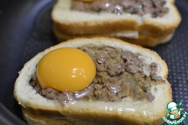 """Выкладываем фарш внутрь бутерброда. Выкладывать нужно так, что бы было как можно меньше пространства между хлебушком и """"рамкой"""", что бы потом яйцо не сильно вытекало. Разбиваем сверху яйцо, стараясь сохранить целым желток, слегка подсаливаем Даже если белок немного вытечет-ничего страшного. Отправляем в разогретую до 180 град духовку минут на 10, затем присыпаем раскрошенной брынзой или натертым сыром и отправляем в духовку минут на 5. Ориентируйтесь по своей духовке. Наша задача- что бы яйцо получилось """" В мешочек""""."""