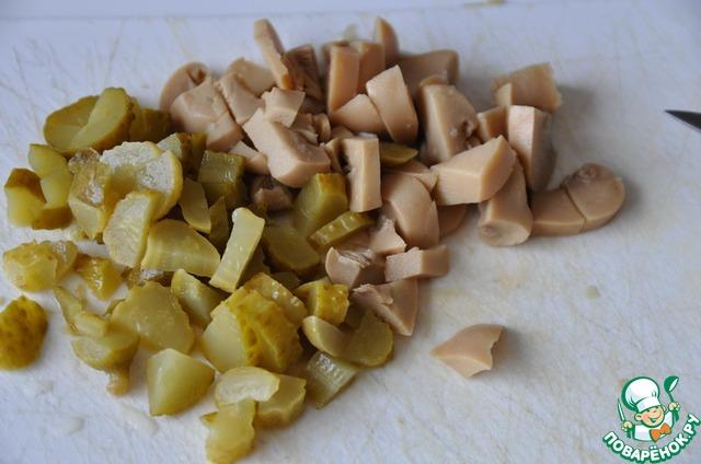 Режем кубиками маринованные шампиньоны и огурцы (корнишоны). Кладём сверху картофеля, промазываем соусом.