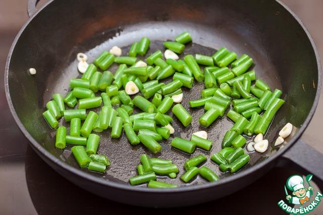 На небольшом количестве растительного масла поджарьте тонко нарезанные зубчики чеснока и стручковую фасоль в течение 5 минут. Если фасоль длинная, разрежьте ее на небольшие кусочки.