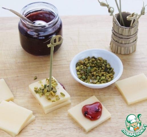 Кусочки сыра посыпать черным перцем. Половину сыра смазать клубничным конфитюром и сложить по по два кусочка друг на друга, посыпать рубленными фисташками и слегка их прижать.