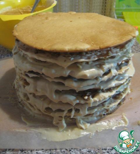 Кладем последний медовый корж, чуть обмазываем бока торта кремом.   Оставшийся крем накрываем пленкой, чтобы пленка касалась крема, и убираем в холодильник.     Он понадобится для смазывания верха и боков торта, после того, как он настоится и чуть осядет.    А торт оставляем на 6-8 часов пропитаться при комнатной температуре (у меня стоял ночь, первые 3 часа на верх торта я положила лист пергамента и увесистую разделочную доску, затем ее убрала).