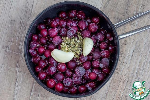 Ягоды крыжовника чистим от хвостиков (в моем случае это было сделано ещё до заморозки ягод). Кладем в сотейник ягоды, сухие травы, дольки чеснока.