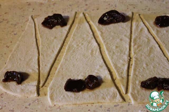 Тесто разделить на 4 части. Каждую часть теста тонко раскатать в пласт 20х40 см, вырезать ножом треугольники. На широкий край положить начинку, я взяла джем из айвы. И свернуть рогалики.