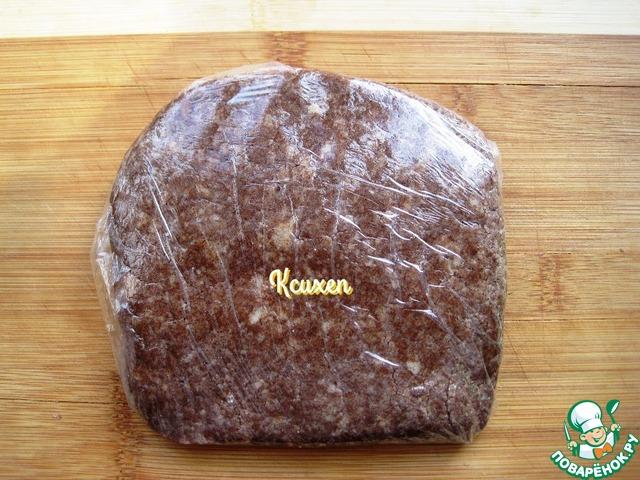 На доске расстилаем пищевую плёнку, высыпаем песочную крошку и, легонько сжимая, заворачиваем тесто в плёнку, формируя не толстую лепёшку. В тесте заметны вкрапления малюсеньких кусочков сливочного масла. Убираем тесто на 1 час в холодильник.