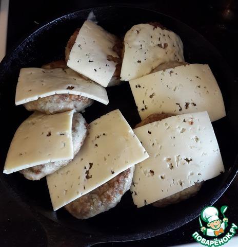Удалите лишнее масло из сковороды, на каждую котлету положите по ломтику сыра. Сыр может быть любой - плавленный ломтиками тоже подойдет!