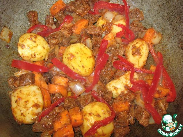 К мясу добавить лук, морковь, томатную пасту, обжарить. Затем добавить картошку - целую, сладкий перец. Всё обжарить на большом огне.