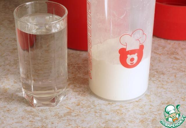 В емкость для приготовления высыпать пакет сухого йогурта. Постепенно доливая теплую воду, размешать, что бы не было комочков. В инструкции написано - влить всю воду, закрыть крышкой и взболтать. Мне такой способ показался неудобным, я перемешивала с помощью венчика, постепенно вливая воду.