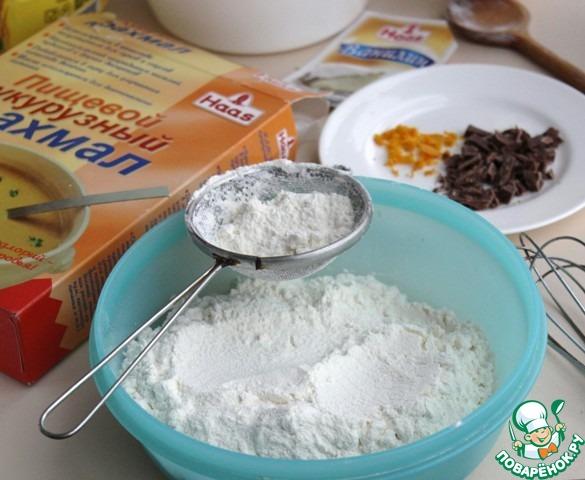 Просеять муку с крахмалом, содой, хорошо перемешать венчиком, добавить натертую цедру и нарубленный шоколад, снова перемешать.   Соединить масляную массу с сухой смесью, размешать.