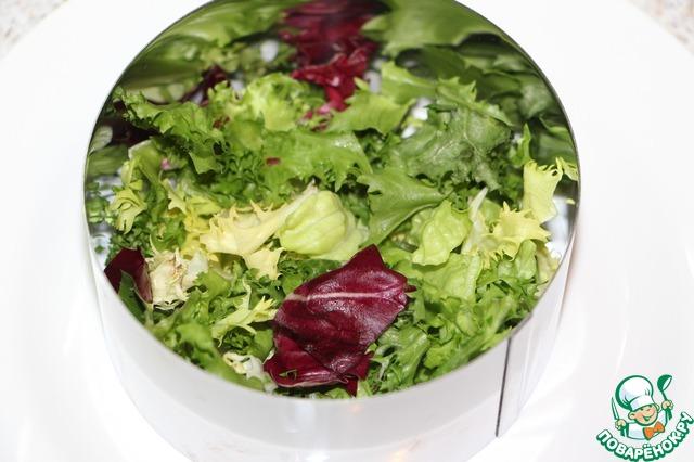На порционную тарелку положить сервировочное кольцо, первым слоем выложить салатные листья