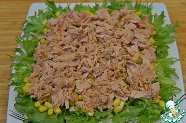 Мясо тунца извлечь из баночки и немного размельчить вилкой. Выложить на кукурузу.