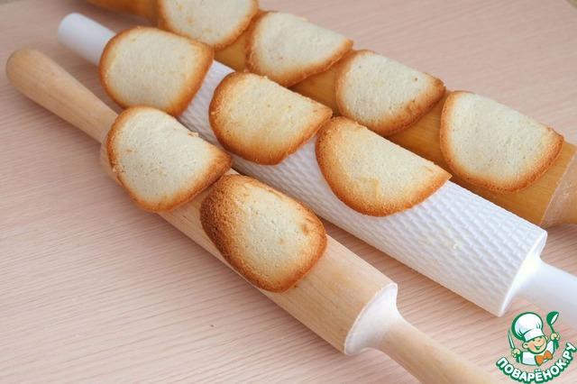 Готовое, еще горячее печенье поместить на скалку для придания изогнутой формы.