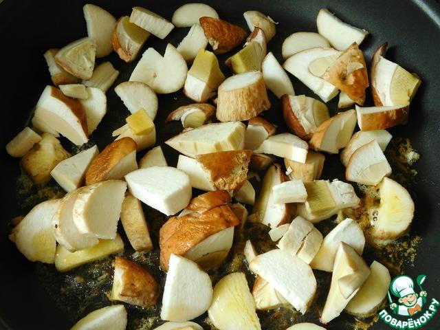 На сковороде растапливаем 2 столовые ложки сливочного масла, выкладываем крупно нарезанные белые грибы и немного их обжариваем, не накрывая сковороду крышкой.