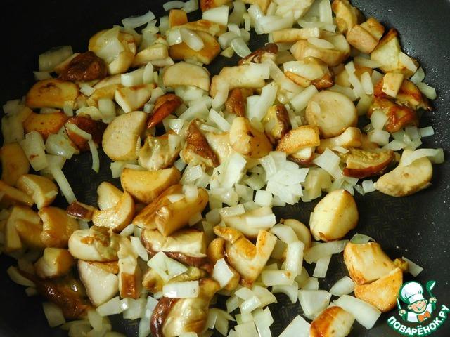 Лук мелко режем, добавляем к грибам, продолжаем обжаривать без крышки, пока лук не станет прозрачным, затем накрываем сковороду крышкой и готовим под крышкой 10 минут на медленном огне.