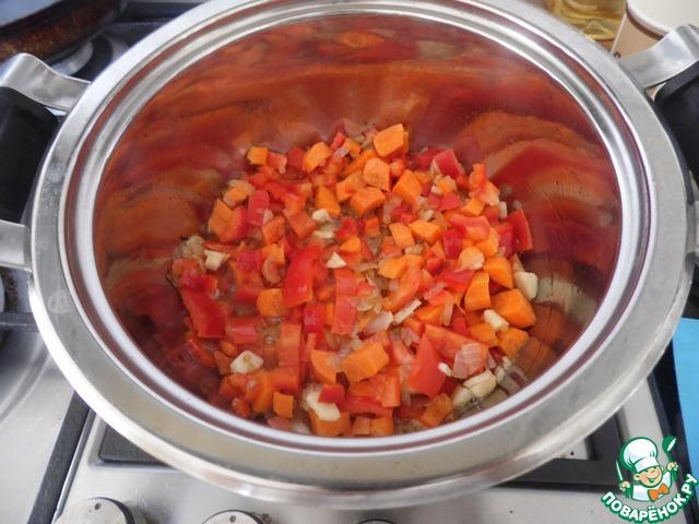 Нарезаем лук, морковь, перец, чеснок. В кастрюле с толстым дном разогреваем 2 ст. л. растительного масла. Выкладываем лук, морковь, чеснок и перец и жарим на среднем огне, помешивая, около 4 минут.