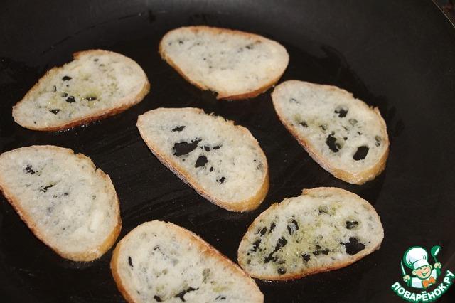 Багет порезать тонкими ломтиками, подсушить на сковороде