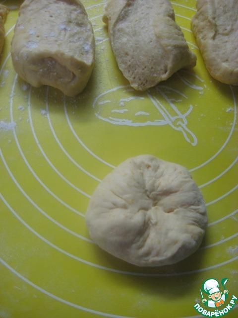 Припыляем стол мукой, выкладываем тесто, чуть обминаем его, делим на равные кусочки (приблизительно).       Берем один кусочек, делаем из него лепешку и начинаем собирать края лепешки в центре, формируя булочку.