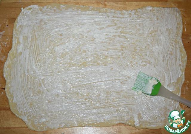Присыпать рабочую поверхность и тесто мукой. Раскатать круглую заготовку в тонкий прямоугольный пласт (примерно 28х33 см). Тесто раскатать как можно тоньше, тем более, что это совсем не трудно. Тесто очень легко раскатывается, но не рвется.    Смазать пласт размягченным сливочным маслом (1/3 часть от 100 г)