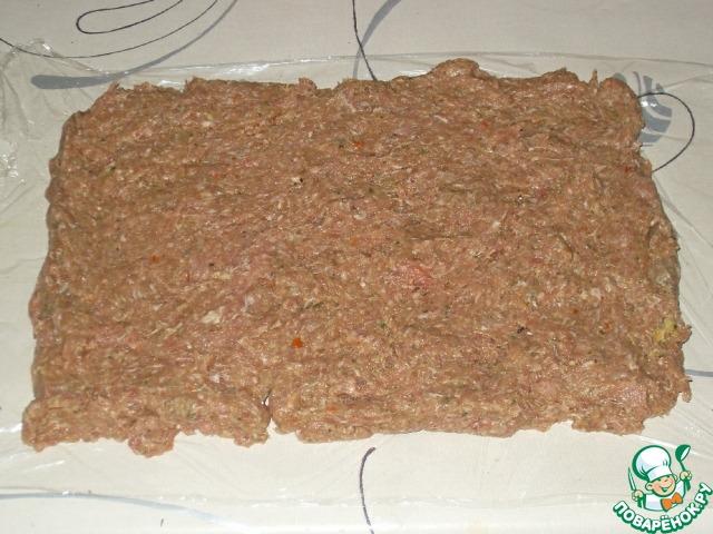 Кусок пленки смазать растительным маслом и разложить фарш в виде толстенького прямоугольника.