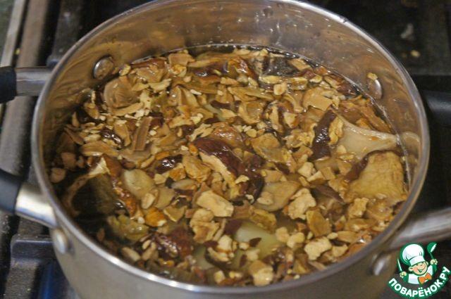 Картофель очистить, нарезать крупными кубиками.   Сухие грибы промыть.     Сложить картофель и грибы в сотейник, залить небольшим количеством воды и варить после закипания 10 минут, до полуготовности.     Отвар слить, грибы мелко нарезать.