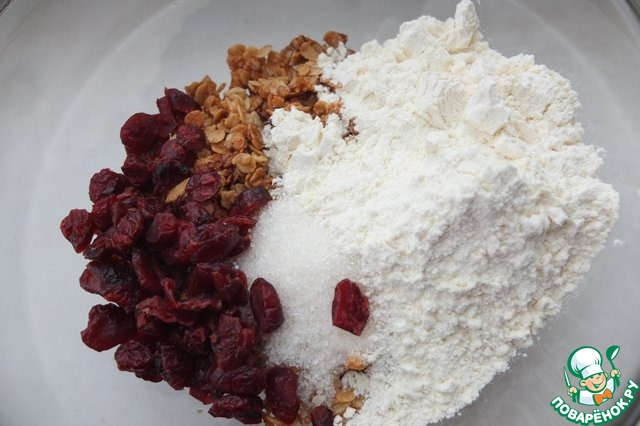 Пересыпаем обжаренные хлопья в миску, добавляем оставшийся сахар, клюкву, просеянную муку.       Вместо клюквы можно добавить любые сухофрукты, измельченные орехи, кусочки шоколада.