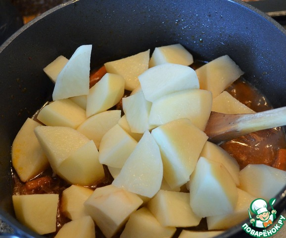 Картофель почистить и нарезать кусками по размеру мяса.   Выложить в казан.    Тушить на среднем огне.
